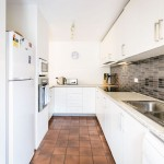 Kitchen area with white cabinetry