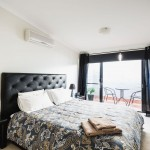 Bedroom with black leather bed and outside patio